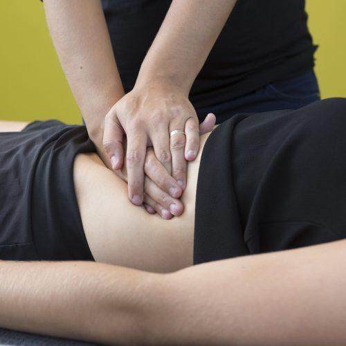 therapeut drukt met beide handen ter hoogte van middenrif van patient